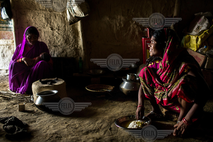 25 year old Sri Kanthi Devi squats down to eat her lunch as her infant son lies in the arms of her sister in law, Lal Chuni Devi, in their kitchen in Ramgarwa village.