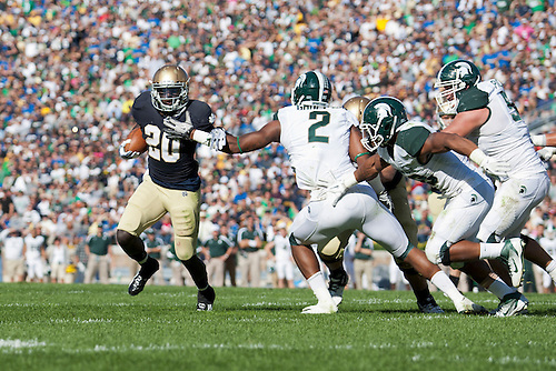 Notre Dame running back Cierre Wood (#20) turns the corner around Michigan State defenders on his way to a touchdown in action during NCAA football game between Notre Dame and Michigan State.  The Notre Dame Fighting Irish defeated the Michigan State Spartans 31-13 in game at Notre Dame Stadium in South Bend, Indiana.