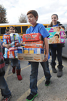 NWA Democrat-Gazette/FLIP PUTTHOFF <br /> Ryan Gray (center), student at Elza Tucker Elementary in Lowell, carries food items with other fifth-graders Tuesday Nov. 24, 2015 into Lowell First Baptist Church. Students in Candace Pierce's fifth-grade class organized a food drive that saw more than 3,800 food items donated.