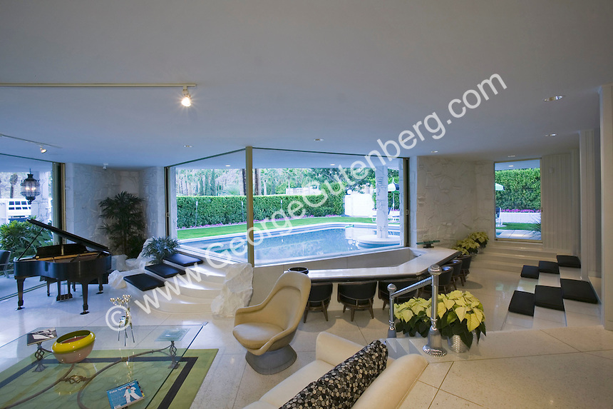 Contemporary living room with tile floors and pool view in background