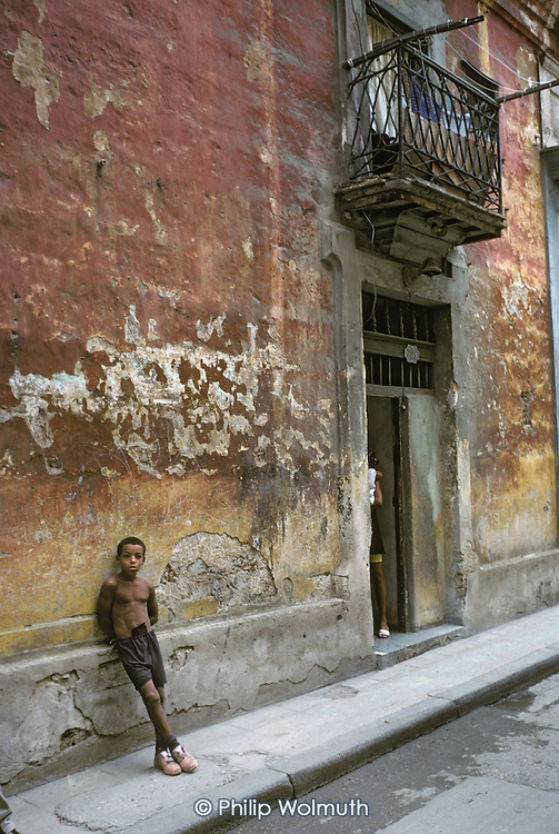 A young boy outside his home in a crumbling street in Old Havana (Havana Viejo).
