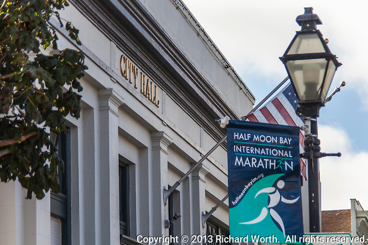 A banner for the Half Moon Bay International  Marathon hangs from a lightpost in front of City Hall in Half Moon Bay, California.  The marathon will be run September 29, 2013