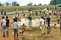 Kenya. Rift Valley Province. Matisi.Maize bags are on the ground and ready to be carried on a truck. The children play near the concrete road. A crowd of people walk. © 2004 Didier Ruef