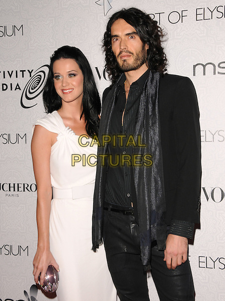 "KATY PERRY & RUSSELL BRAND .at Art of Elysium 3rd Annual Black Tie charity gala '""Heaven"" held at 990 Wilshire Blvd in Beverly Hills, California, USA, January 16th 2010 .                                                                  arrivals half length white dress one shoulder silver clutch bag grecian couple black scarf jacket shirt blazer shiny beard facial hair .CAP/RKE/DVS.©DVS/RockinExposures/Capital Pictures"