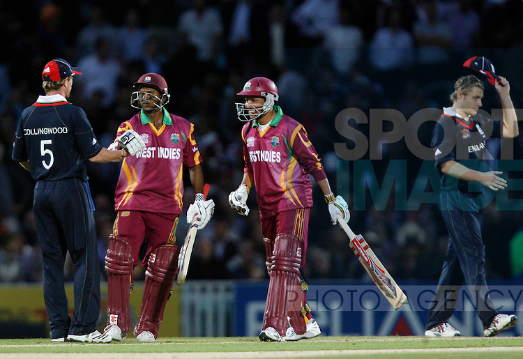 West Indies' Ramnaresh Sarwan and Shivnarine Chanderpaul celebrate victory over England by 5 wickets with 3 balls to spare as Paul Collingwood offer his congratulations.