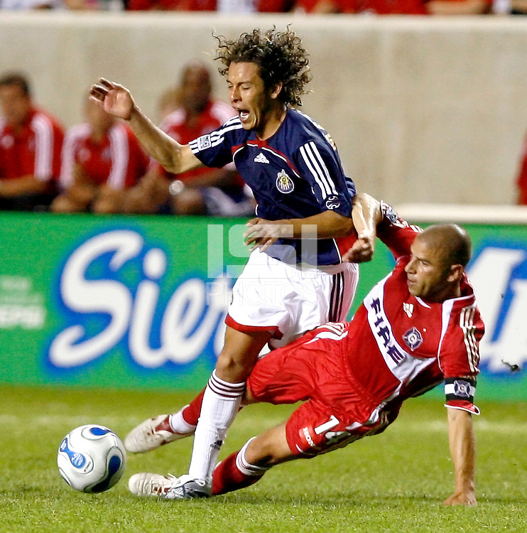 Chicago Fire midfielder Chris Armas (14) trips Chivas USA midfielder Francisco Mendoza (6).  Chivas USA defeated the Chicago Fire 2-1 at Toyota Park in Bridgeview, IL on August 12, 2006.