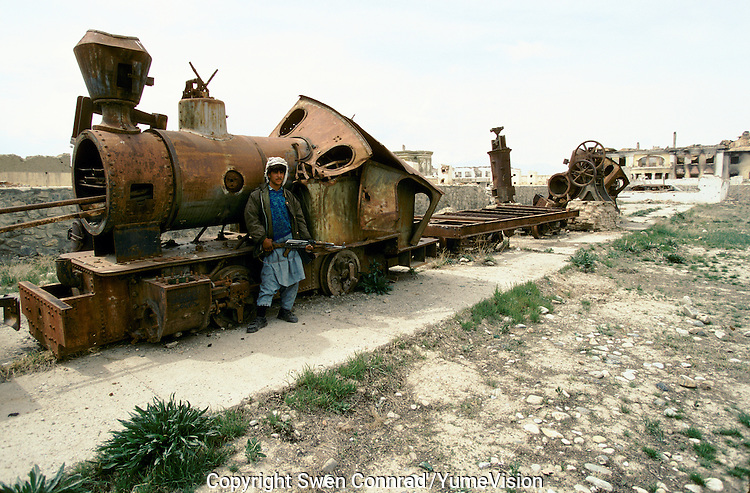 A young Mudjahedin next to a train engine and a coach in the backyard of the National Museum in 1995..Under the Rabani and Massoud government in 1992-1996, the National Museum was  completely loot and destroy. .Kabul, Afghanistan.