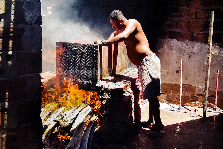 A Brazilian man controls the slow boiling process in the metal pot loaded with shrimps on the yard of a dried shrimp manufacure in Pontal do Peba, Brazil, 13 March 2004.