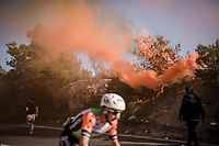 thik smoke once again covers the Capo Berta passage of the riders > but this time year the bushes catch fire (!! 🔥) and flair up just as the riders ride by<br /> <br /> 110th Milano-Sanremo 2019 (ITA)<br /> One day race from Milano to Sanremo (291km)<br /> <br /> ©kramon