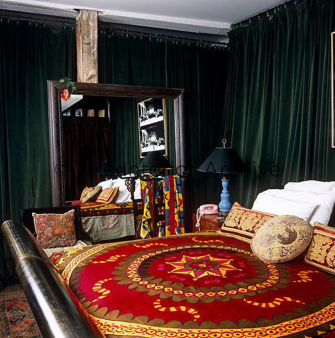 The bedroom is separated from the rest of the loft by green velvet curtains and furnished with a large bronze bed