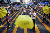 Commuters walk between barricades and miniature paper umbrellas, symbols of pro-democracy movement in the area occupied by protesters in Mongkok shopping district in Hong Kong October 30, 2014. A member of China's central bank's advisory body warned on Wednesday that Beijing will punish Hong Kong if pro-democracy protests that have paralyzed parts of the Chinese-controlled financial center for a month are allowed to continue.   REUTERS/Damir Sagolj (CHINA)