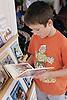 Primary school boy choosing book to read,