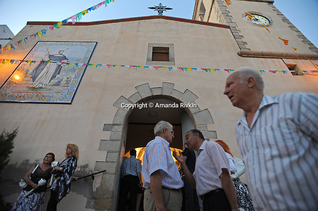 Villagers attend mass before the start of a procession towards the cavalry and cemetery during the municipal fiestas in Costur, Spain on August 16, 2009.