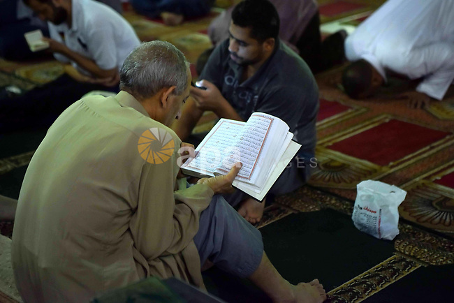 An Egyptian man reads a copy of the Koran, Islam's holiest book, on the Muslim holy fasting month of Ramadan at Amr Ibn al-Aas mosque, in Cairo on May 30, 2017. Ramadan is sacred to Muslims because it is during that month that tradition says the Koran was revealed to the Prophet Mohammed. The fast is one of the five main religious obligations under Islam. More than 1.5 billion Muslims around the world will mark the month, during which believers abstain from eating, drinking, smoking and having sex from dawn until sunset. Photo by Amr Sayed