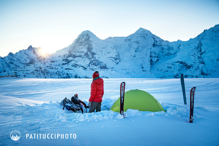 A woman stands next to her tent and watches the sunrise next to the Eiger in the Jungfrau Region of Switzerland.