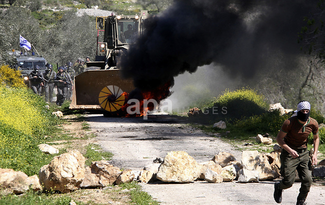 Palestinian youths hurlsl stones at Israeli security forces during a protest in the village of Kufr Qaddum near the Israeli settlement of Kdumim, in the northern West Bank, Friday, March 9, 2012.  Photo by Wagdi Eshtayah