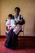 36 year old Rasenthiram Sasikala poses for  photo with her children and the CHDR- Child Health Development Record Card (immunization/vaccination card) in Punaineeravi Village in Kilonochchi, Sri Lanka.  Photo: Sanjit Das/Panos