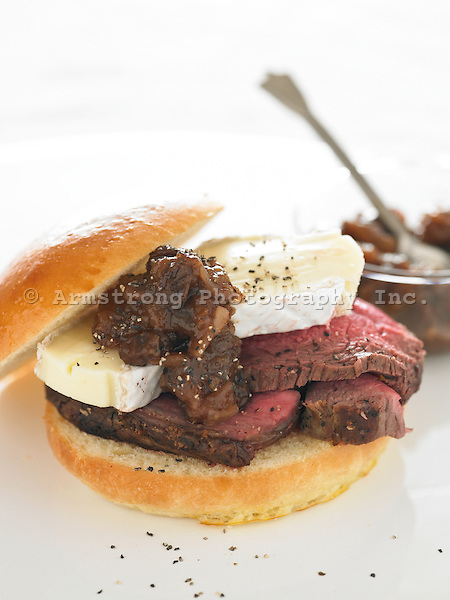 Slices of beef tenderloin and brie cheese on a brioche roll.