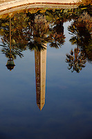 The reflected image of an obelisk, of a street lamp and of the surrounding trees on the perfectly flat water surface of a basin in villa Torlonia, Rome. Digitally Improved Photo