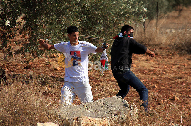 Palestinian youths hurl stones towards Israeli soldiers during a protest against Israel's separation barrier as masked Palestinian stones throwers clash with Israeli soldiers in the West Bank village of Bilin, near Ramallah, on November 12, 2010. Clashes erupted during the weekly demonstrations, which are aimed at halting the construction of Israel's controversial separation barrier that is mostly built inside the occupied territory and cuts off farmers from their land in border communities like Nilin. Photo by Wagdi Eshtayah