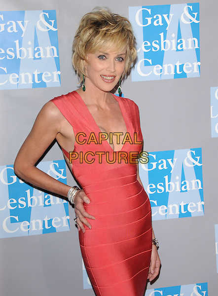 """SHARON STONE .at """"An Evening With Women: Celebrating Art, Music & Equality"""" held at The Beverly Hilton Hotel in Beverly Hills, California, USA, April 24th 2009. .half length red orange coral Herve Leger bandage dress cleavage tight fitting hand on hip.CAP/DVS.©DVS/RockinExposures/Capital Pictures"""