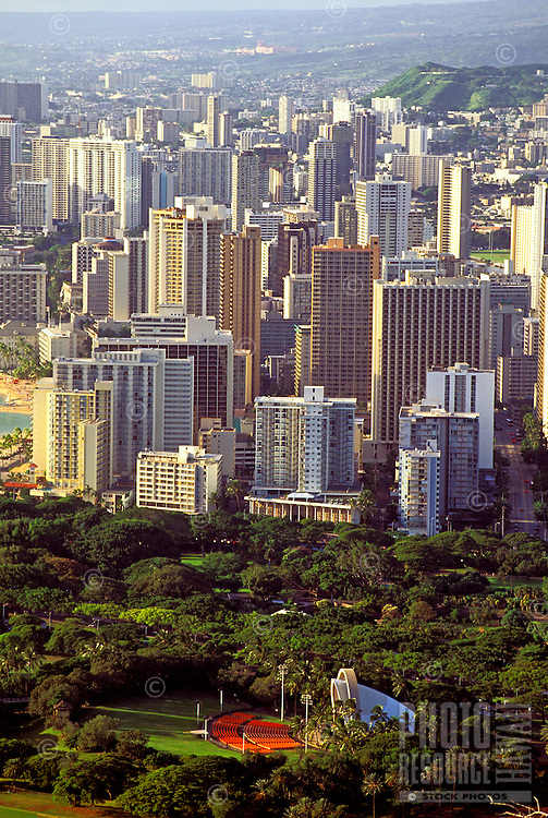 Performance venue Waikiki Shell surrounded by lush trees in Kapiolani Park with Waikiki hotels and condos towering in the background and Punchbowl Memorial in the upper right.