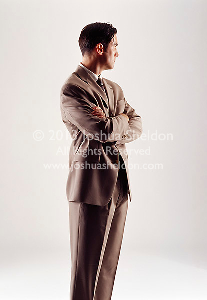 Caucasian looking man wearing a tan suit looking sideways