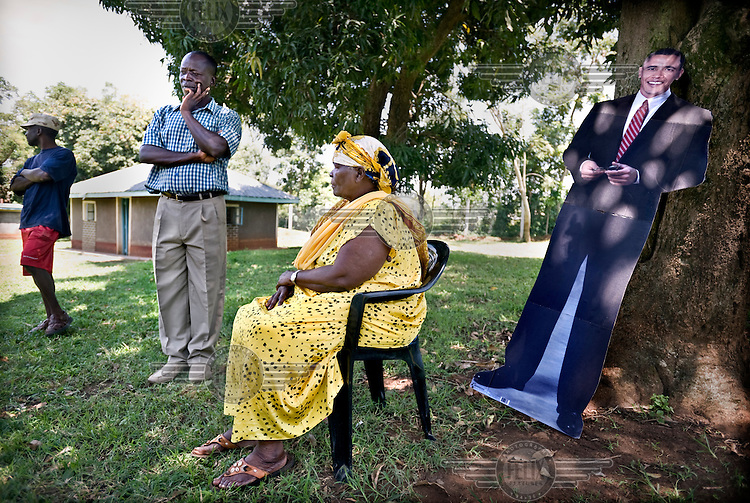 Sarah Hussein Obama, the grandmother of US presidential candidate Barack Obama, whose father was born and brought up here in the village of Nyangoma Kogelo. On the left is Obama's step uncle, Said Obama and on the right a lifesize picture of the presidential candidate. Sarah is sitting in the shade of a tree in her garden in front of her house.