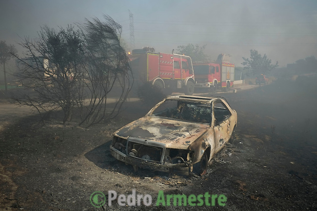A burnt car is pictured as smoke billows from properties in background at the site of a wildfire in Tres Cantos, north of Madrid on August 22, 2013. © Pedro ARMESTRE.