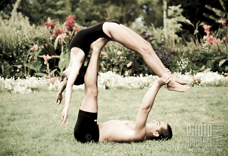 Couple practicing yoga at a outdoor park