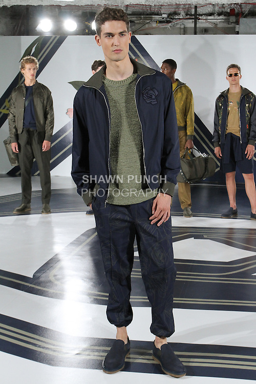Model Jason poses in a tech-nylon track jacket in Navy, Nylon sweater in Agave, and graphic rose print jogger in navy, from the Perry Ellis Spring 2017 collection by Michael Maccari, on July 11th 2017, during New York Fashion Week Men's Spring Summer 2017.