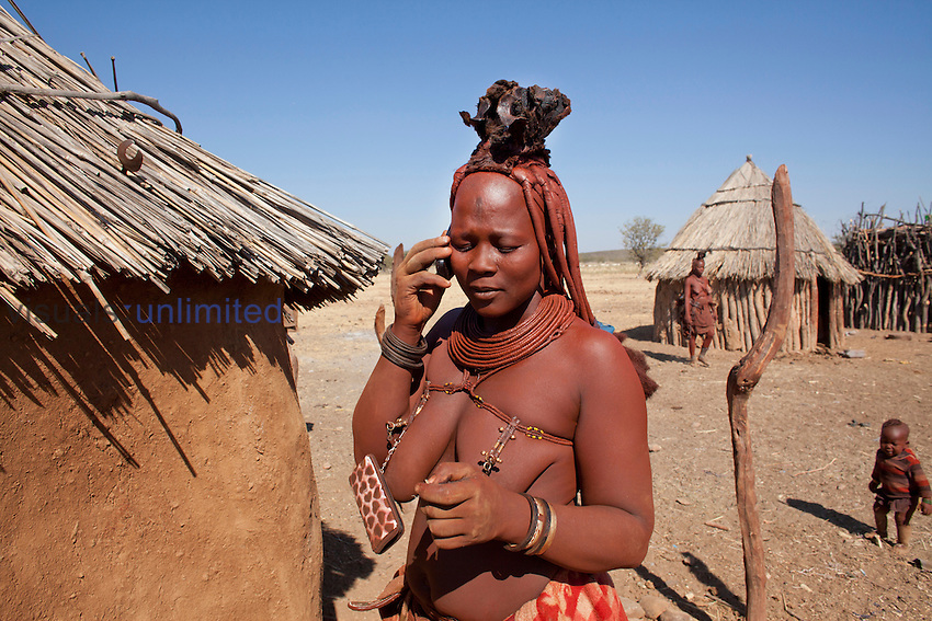 Himba tribe woman on cellphone, Namibia.