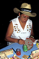 Woman artisan painting wooden handicrafts from El Salvador, Central America