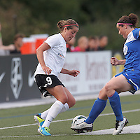 Boston Breakers defender Rhian Wilkinson (7) fails to contact the ball dribbled by Portland Thorns FC forward Danielle Foxhoven (9). In a National Women's Soccer League (NWSL) match, Boston Breakers (blue) defeated Portland Thorns FC (white/black), 2-1, at Dilboy Stadium on August 7, 2013.