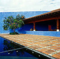 A terrace of terracotta tiles and pebbles separates the swimming pool from the loggia