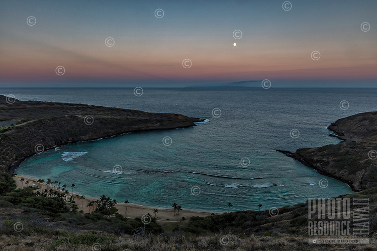 At dusk, the full moon rises over Hanauma Bay, with a distant Moloka'i barely visible through the clouds and haze, Hawai'i Kai, East O'ahu.