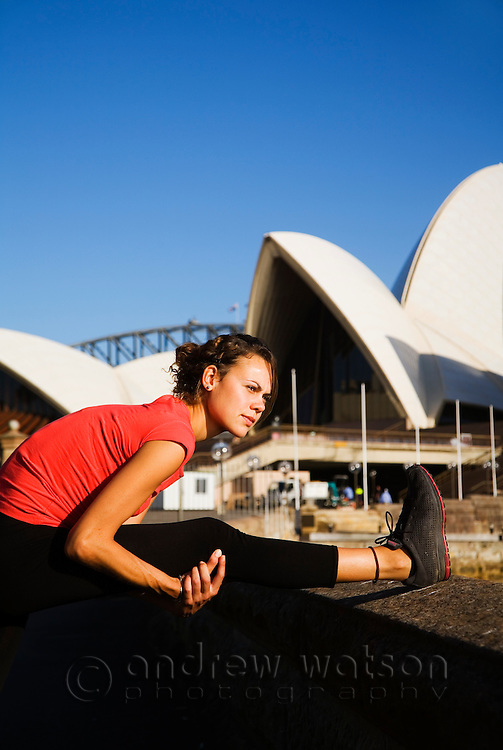 A jogger stretches on the Sydney Harbour waterfront in front of the Opera House.  Sydney, New South Wales, AUSTRALIA.