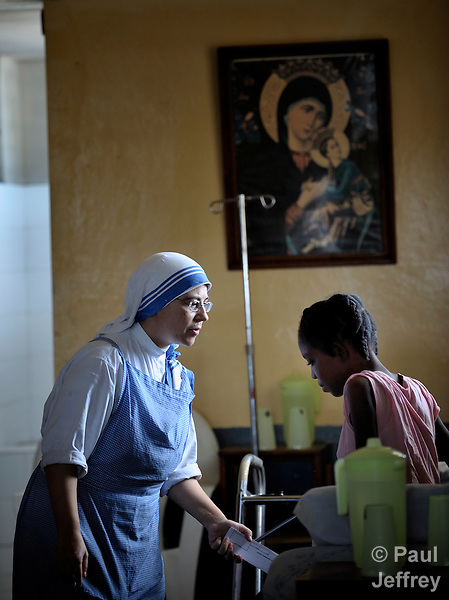 "At the ""House for the Dying"", a hospice for people living with AIDS and other seriously ill patients run by the Sisters of Charity in Port au Prince, Haiti, Sister Paula, a Spanish nun, talks with a patient."