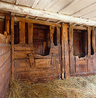 A barn strewn with fresh hay contains a series of ancient animal stalls