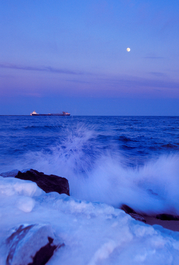THE FREIGHTER ALGOSTEEL ENTERS MARQUETTE'S UPPER HARBOR UNDER A FULL MOON AS LAKE SUPERIOR WAVES CRASH ON AN ICY SHORE IN MARQUETTE MICHIGAN.