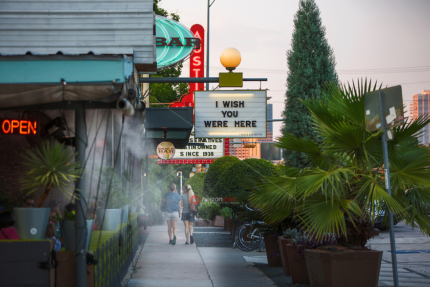 Tourists stroll past the iconic neon signs of South Congress Avenue, a local favorite hip and eclectic neighborhood, called SoCo by the locals - Stock Image.