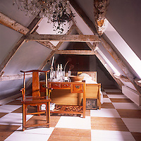 An attic bedroom decorated in blue and white. The room has exposed rafter beams and a painted wooden floor. The room is simply furnished with a double sleigh bed and a wooden chair. A collection of glassware stands on a wood writing desk.