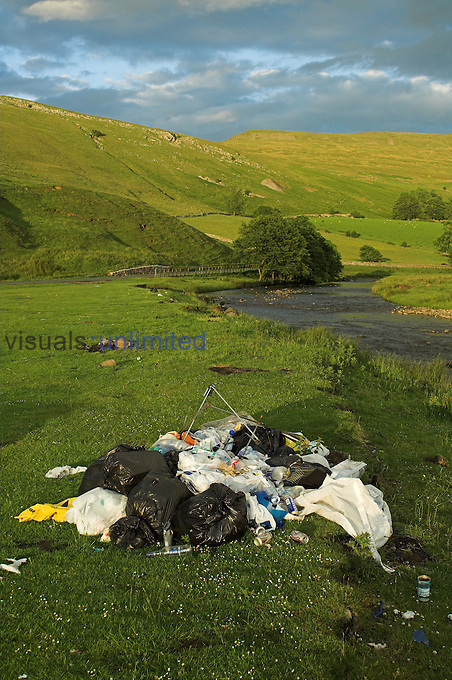 Fly tipping in the countryside , leaving rubbish against a river, Cumbria