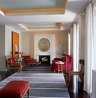 The Art Deco inspired living room has oak floors layered with four different shades of red stain covered with a grey and white striped rug and furnished with red mohair sofas