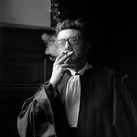 """8 juin 1961. Plan rapproché de Maître Farge (avocat de l'accusé Raymond Peralo) en tenue, vue de face, cigarette à la bouche. Cliché pris dans le cadre de l'affaire de la """"Tournerie des drogueurs"""" dont le procès s'est ouvert à Toulouse le 5 juin 1961. Observation: Affaire de la """"Tournerie des drogueurs"""" : Procès qui s'est ouvert aux assises de Toulouse le 5 juin 1961, sous la présidence de M. Gervais (conseiller doyen). Sur le banc des accusés se trouvent François Lopez, Raoul Berdier, Marie-Thérèse Davergne (Maïté) et d'autres malfaiteurs toulousains (Camille Ajestron, Henri Oustric, Raymond Peralo, Marcel Filiol, Paul Carrère, Charles Davant et François Borja). Outre les accusations pour association de malfaiteurs, ils comparaissent pour l'assassinat de Jean Lannelongue, propriétaire du Cabaret la Tournerie des Drogueurs (rue des Tourneurs) dans la nuit du 3 au 4 janvier 1959, au cours d'une tentative de racket."""