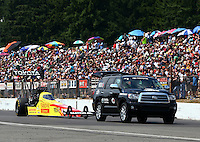 Aug. 2, 2014; Kent, WA, USA; NHRA top fuel dragster driver Antron Brown on the return road in front of the grandstands during qualifying for the Northwest Nationals at Pacific Raceways. Mandatory Credit: Mark J. Rebilas-
