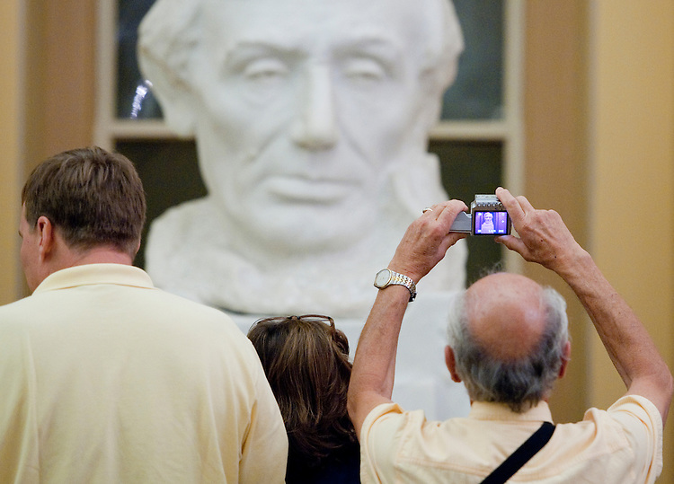 UNITED STATES - JUNE 20: A tourist takes a photo of a large bust of President Abraham Lincoln in the U.S. Capitol Crypt on Monday, June 20, 2011. (Photo By Bill Clark/Roll Call)