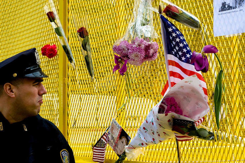 A police officer views the construction site at Ground Zero near a fence decorated with memorials on the day after Osama bin Laden was killed.