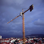 Large construction crane towers over houses of Viana do Castello, Portugal