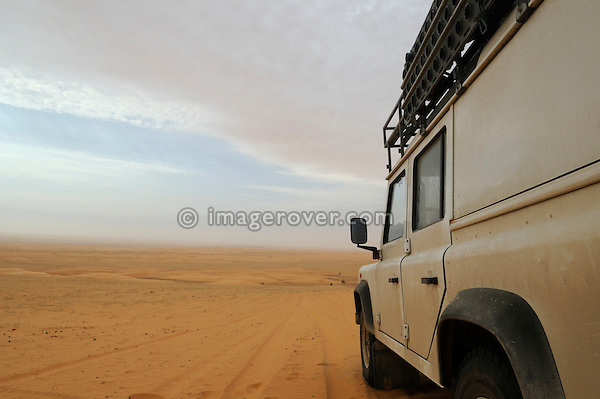 Africa, Mauritania, Sahara Desert, nr. Tidjikdja. Bad weather is approaching while Land Rover Defender TD5 Station Wagon is crossing a sandy plain between Chinguetti and Tidjikdja. --- RELEASES AVAILABLE! Automotive trademarks are the property of the trademark holder, authorization may be needed for some uses.